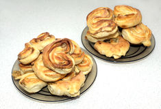 Bollos cocidos sabrosos en las placas en la tabla en cocina Imagen de archivo