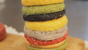 Bollos coloreados multi para la hamburguesa, cierre para arriba Cámara móvil, criticando Pila de bollos coloreados Hamburguesas d metrajes