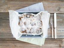 Bollos de canela con la formación de hielo del queso cremoso en un plato de la hornada sobre un ru Imagen de archivo libre de regalías