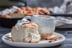 Bollos de canela hechos en casa frescos Rolls con la formación de hielo del queso cremoso Foto de archivo
