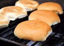 Bollos de hamburguesa en la parrilla Fotos de archivo libres de regalías