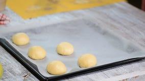 Bollos de la levadura antes de cocer, mentira en el molde para el horno con el papel de la hornada Proceso de cocinar almacen de metraje de vídeo
