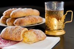 Bollos dulces hechos en casa con el relleno y el té poner crema i de las natillas de la vainilla Foto de archivo libre de regalías