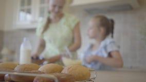 Bollos frescos en la tabla en el fondo de la mamá y poca hija que se divierte junto que hace las crepes o la torta cierre almacen de metraje de vídeo