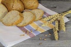 Bollos, granos y oídos del trigo en una tabla de madera Fotos de archivo libres de regalías