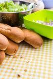 Bollos para los perritos calientes con tocino y la cebolla en el mantel Imagenes de archivo