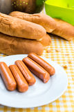 Bollos para los perritos calientes con tocino y la cebolla en el mantel Imagen de archivo libre de regalías