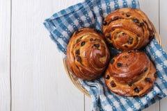 Bollos sabrosos con las pasas en una cesta en un fondo de madera blanco Panadería fresca lugar del desayuno para el texto Visión  imagenes de archivo