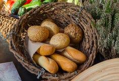 Bollos y baguettes en una tabla en una cesta de mimbre Imagen de archivo
