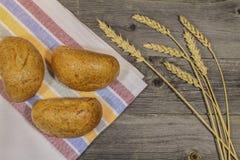 Bollos y oídos del trigo en la tabla Fotografía de archivo libre de regalías