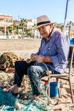 Bolnuevo, Murcia, Spain. An old fisherman is sitting under a parasol because of the heat and is repairing his nets Stock Photo