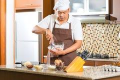 Bolo asiático do cozimento do homem na cozinha home Fotos de Stock Royalty Free