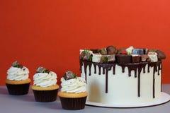 Bolo bonito com crosta de gelo do chocolate e os queques deliciosos fotos de stock
