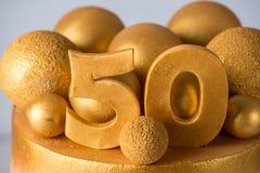 Bolo bonito para o 50th aniversário do casamento decorado com bolas e anéis do ouro Conceito de sobremesas festivas Foto de Stock Royalty Free