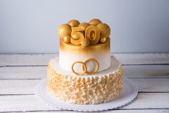 Bolo bonito para o 50th aniversário do casamento decorado com bolas e anéis do ouro Conceito de sobremesas festivas Imagens de Stock Royalty Free