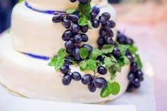 Bolo branco com uvas e as fitas azuis Fotografia de Stock Royalty Free