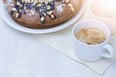Bolo caseiro com porcas e chocolate e dois copos com café na tabela branca de madeira Imagens de Stock Royalty Free
