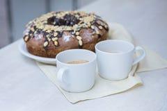 Bolo caseiro com porcas e chocolate e duas xícaras de café na tabela branca de madeira Foto de Stock Royalty Free