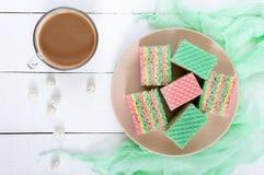 Bolo colorido doce saboroso do waffle do ar e copo do cappuccino em um fundo de madeira branco Foto de Stock Royalty Free