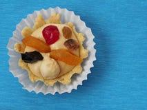 Bolo com creme e fruto da manteiga no bacground azul imagem de stock royalty free