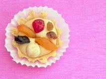 Bolo com creme e fruto da manteiga no bacground cor-de-rosa foto de stock royalty free