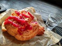 Bolo com doce vermelho bolo do creme com vidro de água tempo ensolarado fotografia de stock royalty free