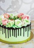 Bolo comemorativo com as rosas feitas do creme em um fundo de madeira branco Foto de Stock Royalty Free