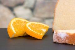 Bolo cortado do limão em uma ardósia decorada com algumas partes de ou Imagens de Stock