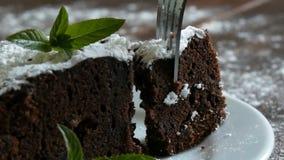 Bolo cozido caseiro da brownie do chocolate abafado com açúcar pulverizado em uma placa branca decorada com folhas de hortelã for vídeos de arquivo