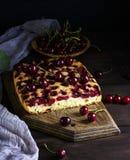 Bolo cozido com cerejas em uma placa de madeira marrom Fotografia de Stock Royalty Free