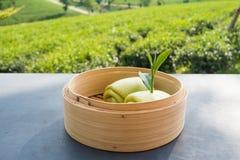 Bolo cozinhado e folhas de chá verdes no bambu golpeado na tabela com fundo da plantação de chá foto de stock