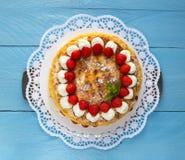 Bolo da merengue com o iogurte da morango na madeira azul Fotos de Stock