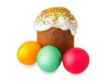 Bolo da Páscoa com o tampão branco da crosta de gelo e do pó colorido, ovos da páscoa pintados isolados no fundo branco tradicion Imagens de Stock
