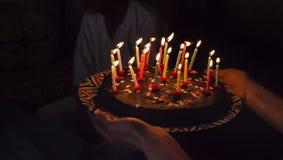 Bolo da surpresa do aniversário com velas na escuridão imagens de stock
