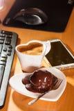 Bolo da xícara de café e de chocolate ao lado do computador fotografia de stock royalty free