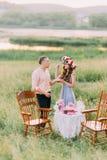 Bolo de alimentação da jovem mulher feliz decorado com as flores cor-de-rosa ao noivo fora Fotos de Stock Royalty Free