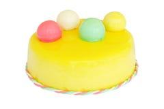 Bolo de aniversário amarelo com as bolas coloridas isoladas no branco Imagem de Stock