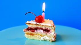 Bolo de aniversário com cereja e vela ardente para o aniversário no fundo azul vídeos de arquivo