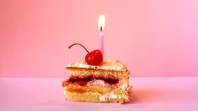Bolo de aniversário com cereja e vela de queimadura para o aniversário no fundo cor-de-rosa video estoque