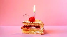Bolo de aniversário com cereja e vela de queimadura para o aniversário no fundo cor-de-rosa Vídeo do lapso de tempo video estoque