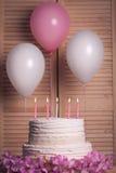 Bolo de aniversário com velas ardentes no fundo de madeira; Fotos de Stock