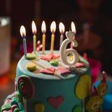 Bolo de aniversário com velas e idade ardentes 6 velas no fundo escuro com os doces na decoração imagem de stock royalty free