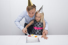 Bolo de aniversário do corte do pai e da filha na tabela foto de stock royalty free