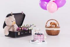 Bolo de aniversário lilás redondo moderno, balões, urso de peluche na mala de viagem do vintage Imagem de Stock