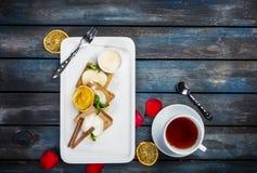 Bolo de areia delicioso com um copo do chá em uma placa branca com pétalas cor-de-rosa Vista superior Fundo de madeira bonito fotografia de stock