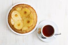 Bolo de cabeça para baixo do abacaxi e copo do chá Fotografia de Stock Royalty Free