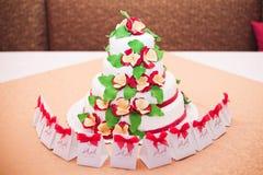 Bolo de casamento branco com as flores vermelhas na tabela Foto de Stock Royalty Free