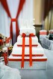 Bolo de casamento branco com fita vermelha Fotografia de Stock Royalty Free