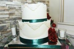 Bolo de casamento com fita verde e a flor vermelha fotografia de stock
