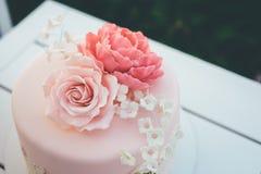 Bolo de casamento cor-de-rosa com geada e rosas do açúcar perto acima foto de stock